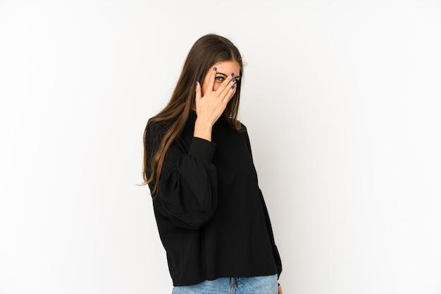 若い白人女性は、恥ずかしい顔を覆っている指で点滅します。