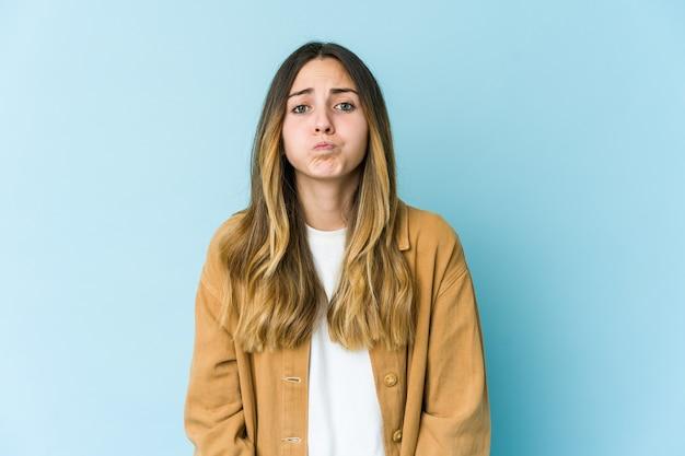 若い白人女性は頬を吹く、疲れた表情をしています。顔の表情のコンセプトです。