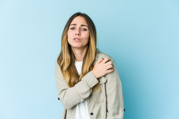 Young caucasian woman on blue having a shoulder pain.