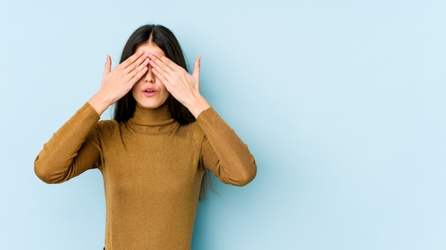 Young caucasian woman on blue wall afraid covering eyes with hands.