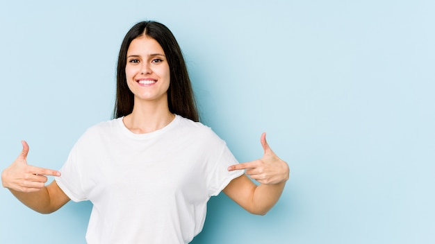 Young caucasian woman on blue wall points down with fingers, positive feeling.