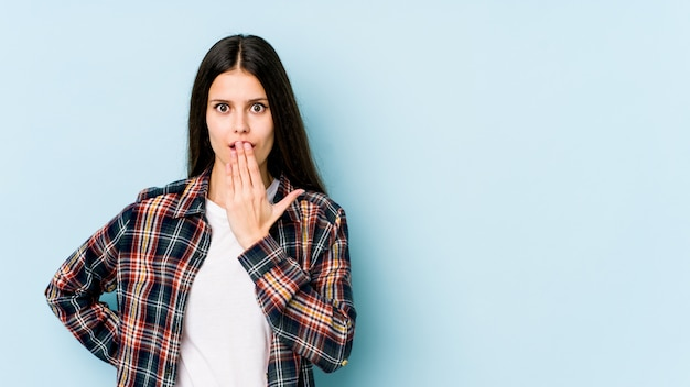 Young caucasian woman on blue wall shocked, covering mouth with hands, anxious to discover something new.
