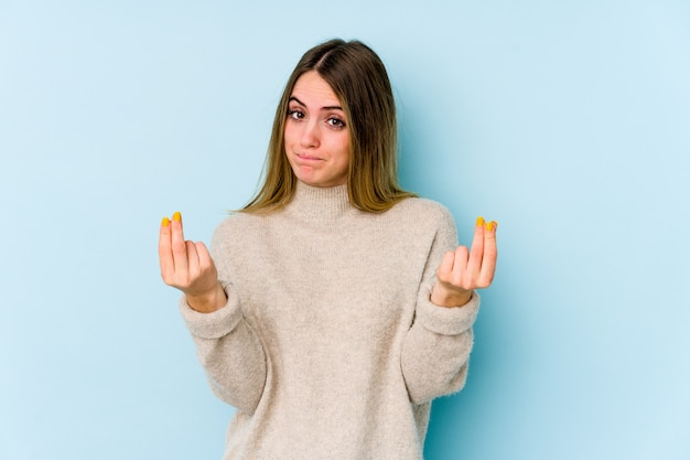 Young caucasian woman on blue wall showing that she has no money.