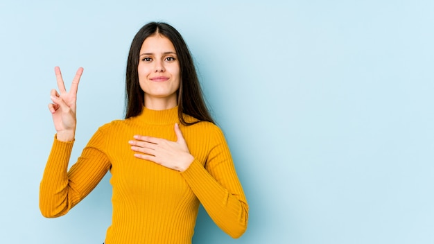 Young caucasian woman on blue wall taking an oath, putting hand on chest.