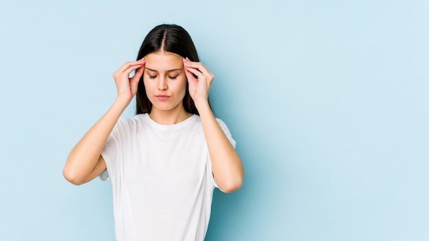 Young caucasian woman on blue wall touching temples and having headache.