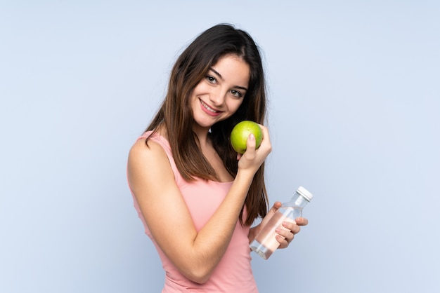 Young caucasian woman on blue wall with an apple and with a bottle of water