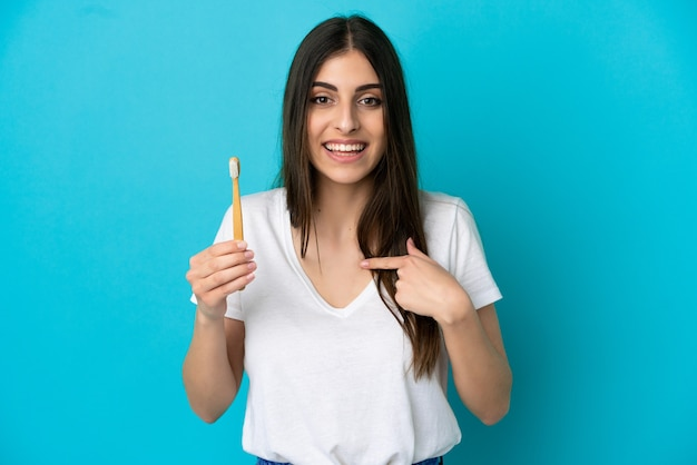 Young caucasian woman brushing teeth isolated on blue background with surprise facial expression