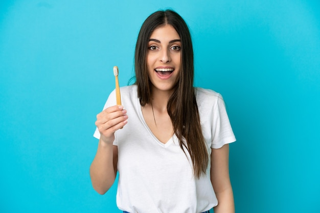 Young caucasian woman brushing teeth isolated on blue background with surprise and shocked facial expression