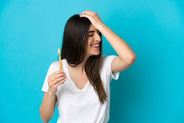 青い背景で隔離の歯を磨く若い白人女性は何かを実現し、解決策を意図しています