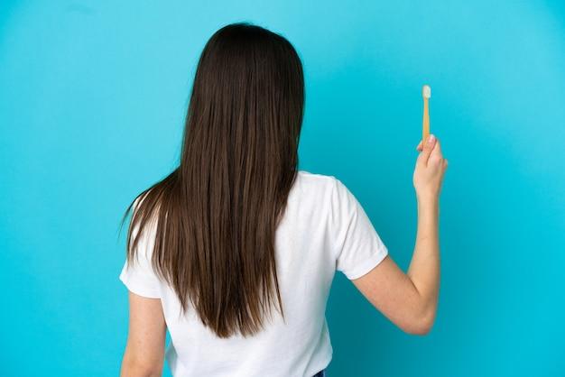 若い白人女性が後ろの位置で青い背景に分離された歯を磨く
