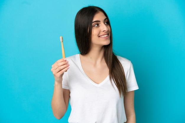 笑顔で見上げる青い背景に分離された歯を磨く若い白人女性