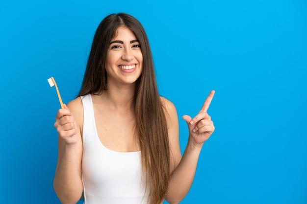 最高の兆候を示して指を持ち上げて青い背景で隔離の歯を磨く若い白人女性 Premium写真