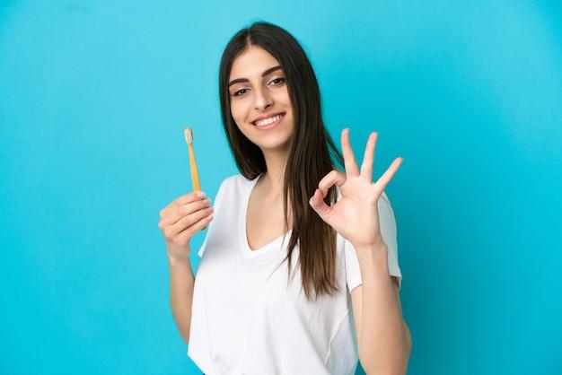 指でokサインを示す青い背景で隔離の歯を磨く若い白人女性