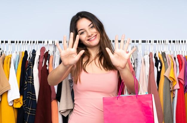 Молодая кавказская женщина покупая некоторые одежды в магазине подсчитывая 10 с пальцами