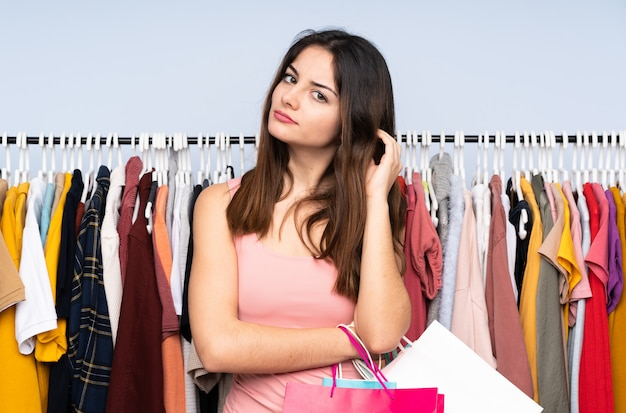 Young caucasian woman buying some clothes in a store having doubts