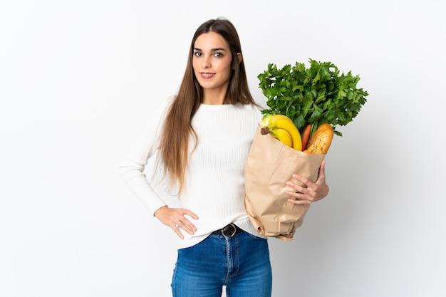 腰に腕と笑顔でポーズをとって白で隔離のいくつかの食品を購入する若い白人女性