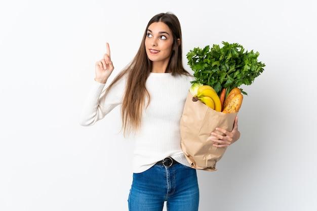 素晴らしいアイデアを指している白い壁に分離されたいくつかの食品を購入する若い白人女性