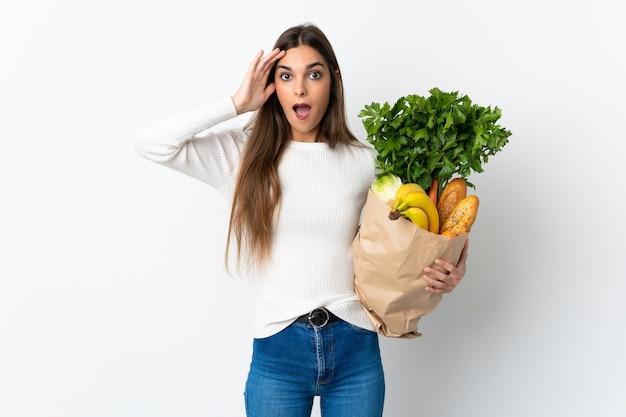 驚きの表情で白い壁に分離されたいくつかの食品を買う白人女性