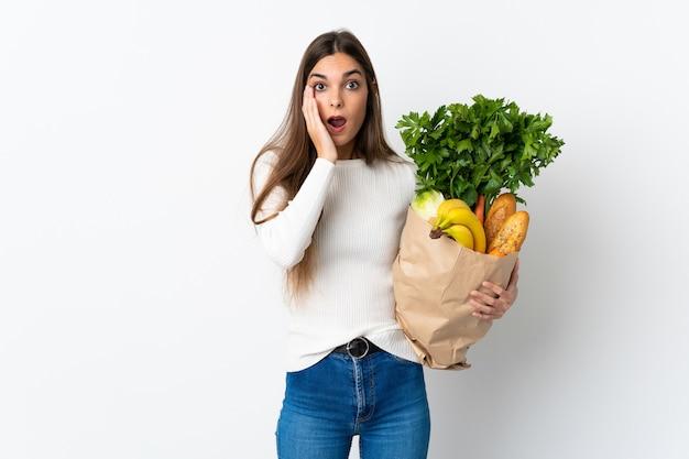 驚きとショックを受けた表情で白で隔離のいくつかの食品を購入する若い白人女性
