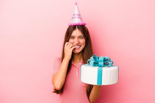 Молодая кавказская женщина празднует день рождения на розовом фоне, кусая ногти, нервная и очень взволнованная.