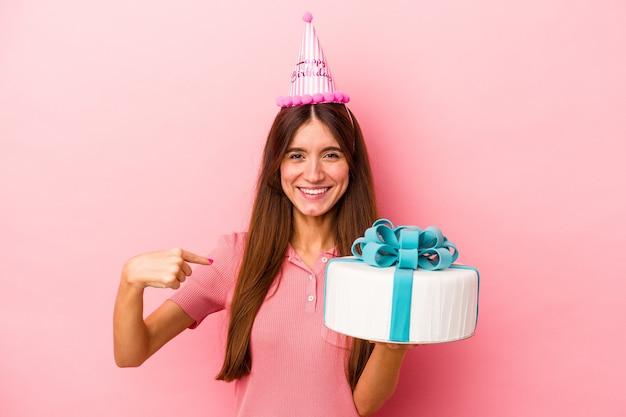 誇りと自信を持って、シャツのコピースペースを手で指しているピンクの背景の人に分離された誕生日を祝う若い白人女性