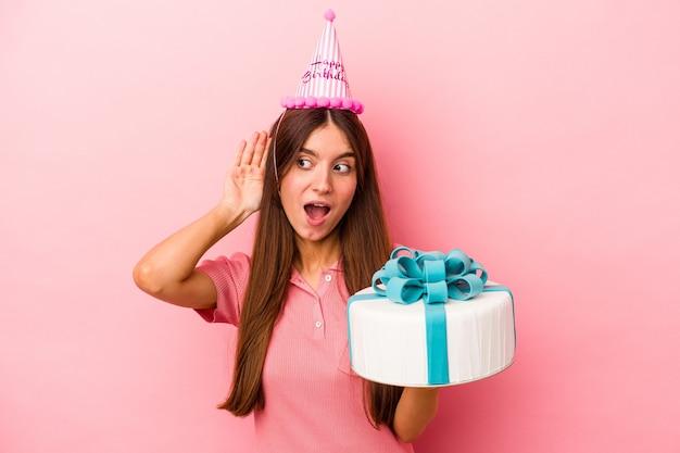 ゴシップを聴こうとしているピンクの背景に分離された誕生日を祝う若い白人女性。