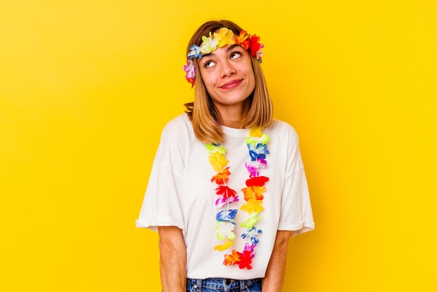 목표와 목적 달성을 꿈꾸는 노란색 벽에 고립 된 하와이 파티를 축하하는 젊은 백인 여자