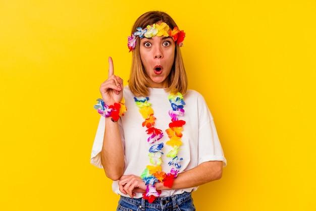 몇 가지 좋은 생각을 가지고 노란색 벽에 고립 된 하와이 파티를 축하하는 젊은 백인 여자