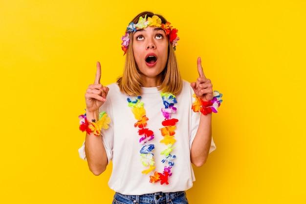 열린 된 입으로 거꾸로 가리키는 노란색 벽에 고립 된 하와이 파티를 축 하하는 젊은 백인 여자.