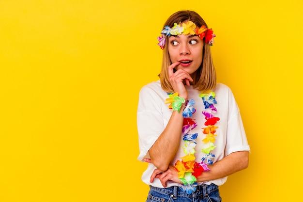 노란색 벽에 고립 된 하와이 파티를 축 하하는 젊은 백인 여자 복사본 공간을보고 뭔가에 대해 편안 하 게 생각.