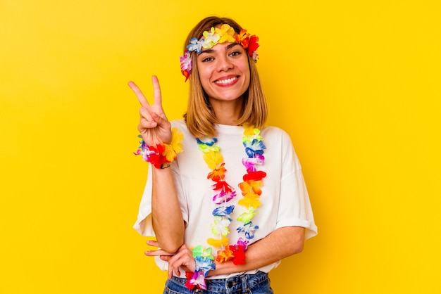 손가락으로 2 번을 보여주는 노란색 벽에 고립 된 하와이 파티를 축 하하는 젊은 백인 여자.