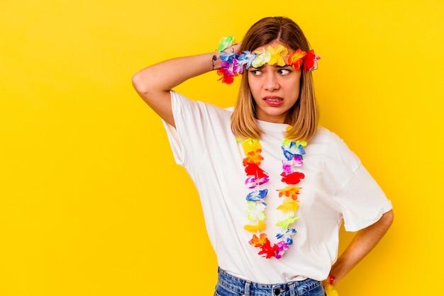 머리 뒤로 만지고, 생각 하 고 선택을 노란색 벽에 고립 된 하와이 파티를 축 하하는 젊은 백인 여자.