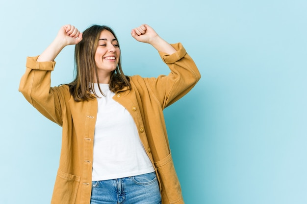 Молодая кавказская женщина празднует особый день, прыгает и поднимает руки с энергией.