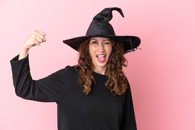 Young caucasian woman celebrating halloween isolated on pink background doing strong gesture