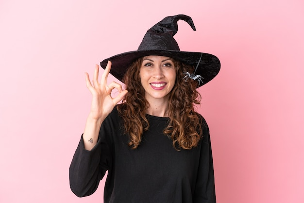 Young caucasian woman celebrating halloween isolated on pink background showing ok sign with fingers