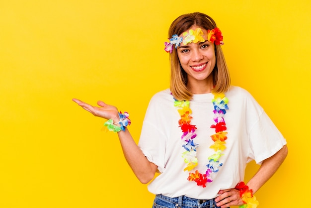 Young caucasian woman celebrating a hawaiian party isolated on yellow wall showing a copy space on a palm and holding another hand on waist.