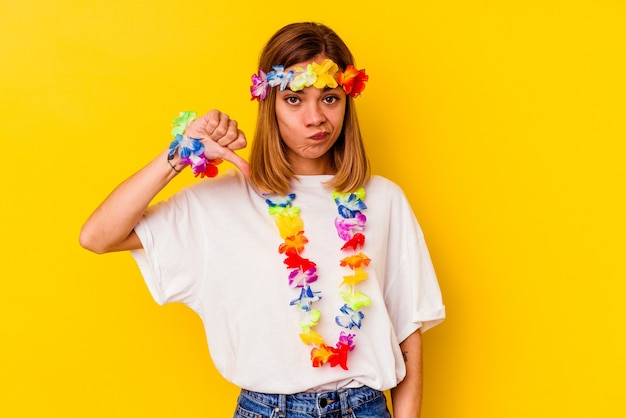 Young caucasian woman celebrating a hawaiian party isolated on yellow wall showing a dislike gesture, thumbs down. disagreement concept.