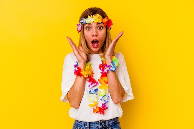 Young caucasian woman celebrating a hawaiian party  surprised and shocked.