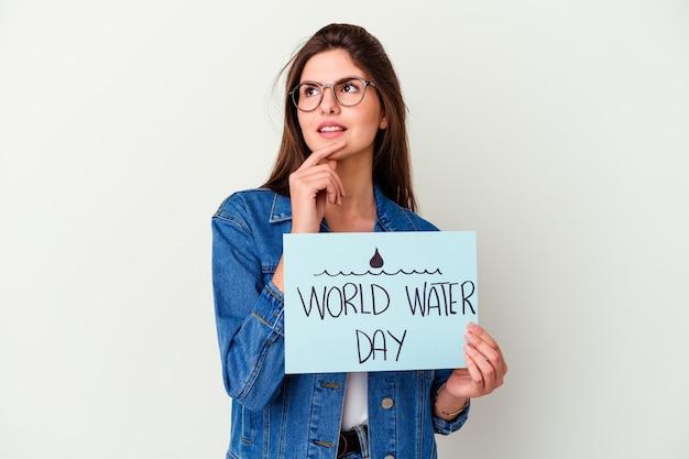 의심스럽고 회의적인 표정으로 옆으로 찾고 분홍색에 고립 된 세계 물의 날을 축하하는 젊은 백인 여자.
