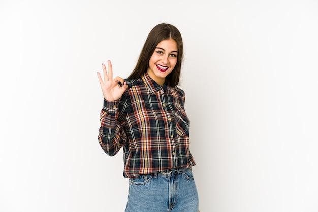 Молодая кавказская женщина жизнерадостная и уверенная, показывая одобренный жест.