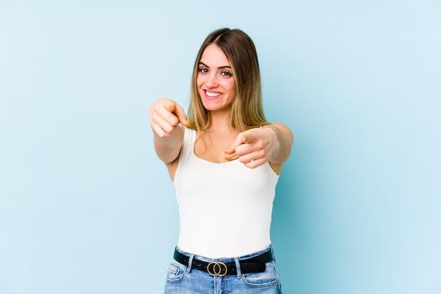 前面を指している若い白人女性の陽気な笑顔。