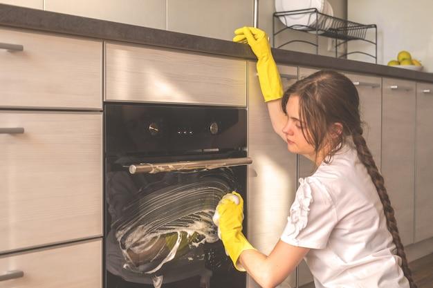 젊은 백인 여성 청소 오븐, 고무 장갑에 손, 아파트 유지 관리 개념 배경 사진