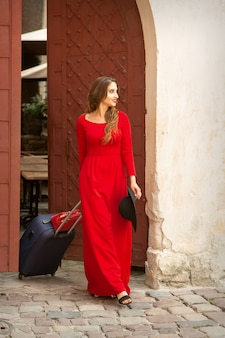 Young caucasian woman comes out of the ancient door with baggage wearing long red dress on the old city street