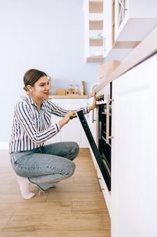 Молодая кавказская женщина готовит на кухне дома, открывая духовку и заглядывая внутрь.