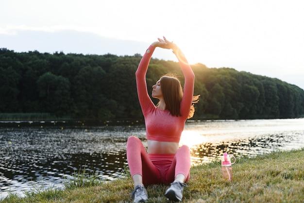 Молодая кавказская женщина делает активные тренировочные упражнения на коврике для йоги у реки летом. концепция здорового образа жизни