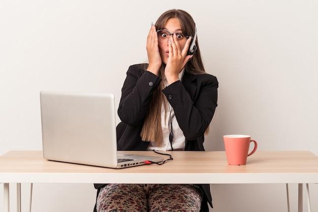 白い背景で隔離の在宅勤務をしている若い白人女性は、おびえ、神経質な指を点滅します。