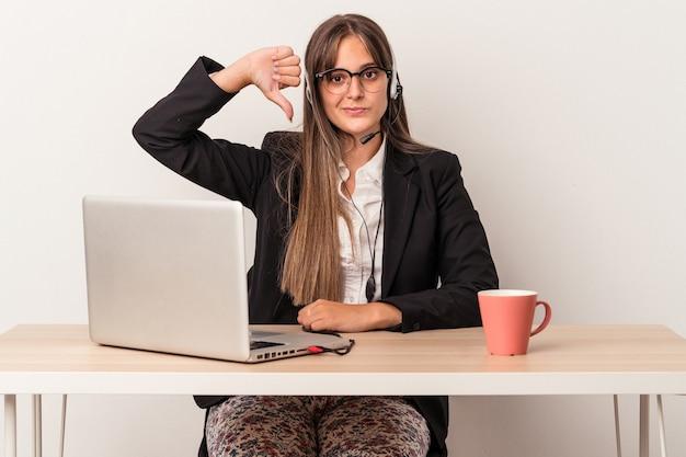 嫌いなジェスチャーを示す白い背景で隔離の在宅勤務をしている若い白人女性は、親指を下に向けます。不一致の概念。