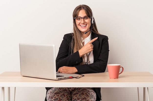 空白のスペースで何かを見せて、笑顔で脇を指して、白い背景で隔離の在宅勤務をしている若い白人女性。