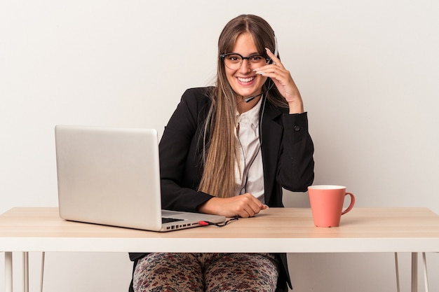 Young caucasian woman doing telecommuting isolated on white background blink at the camera through fingers, embarrassed covering face.