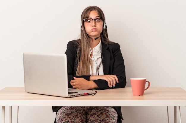 Young caucasian woman doing telecommuting isolated on white background blows cheeks, has tired expression. facial expression concept.